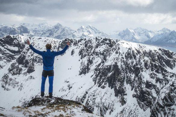 Står med hendene i været på fjelltoppen Stålberget.